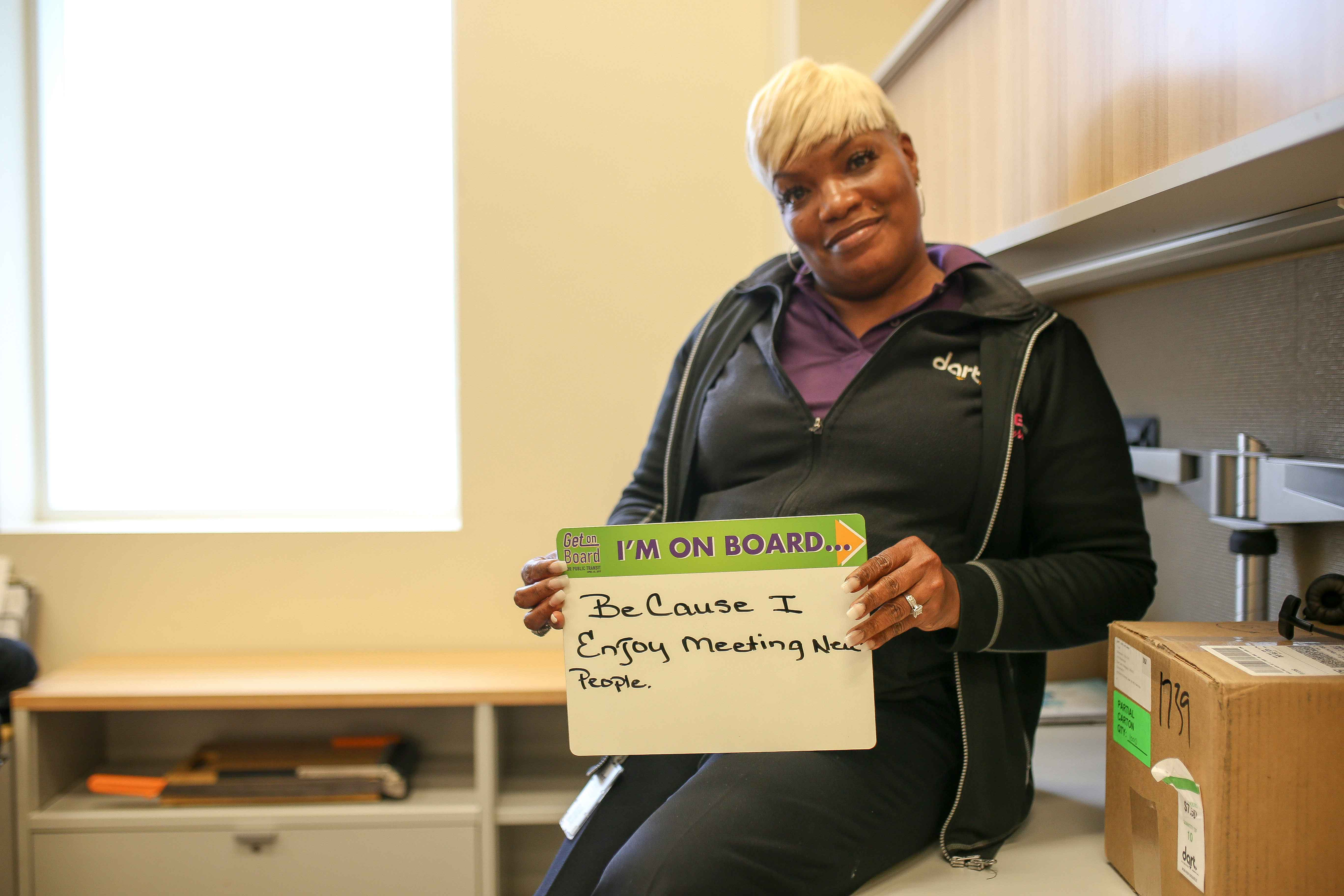 "Woman rests against desk hold sign reading ""I'm on board because I enjoy meeting new people."""