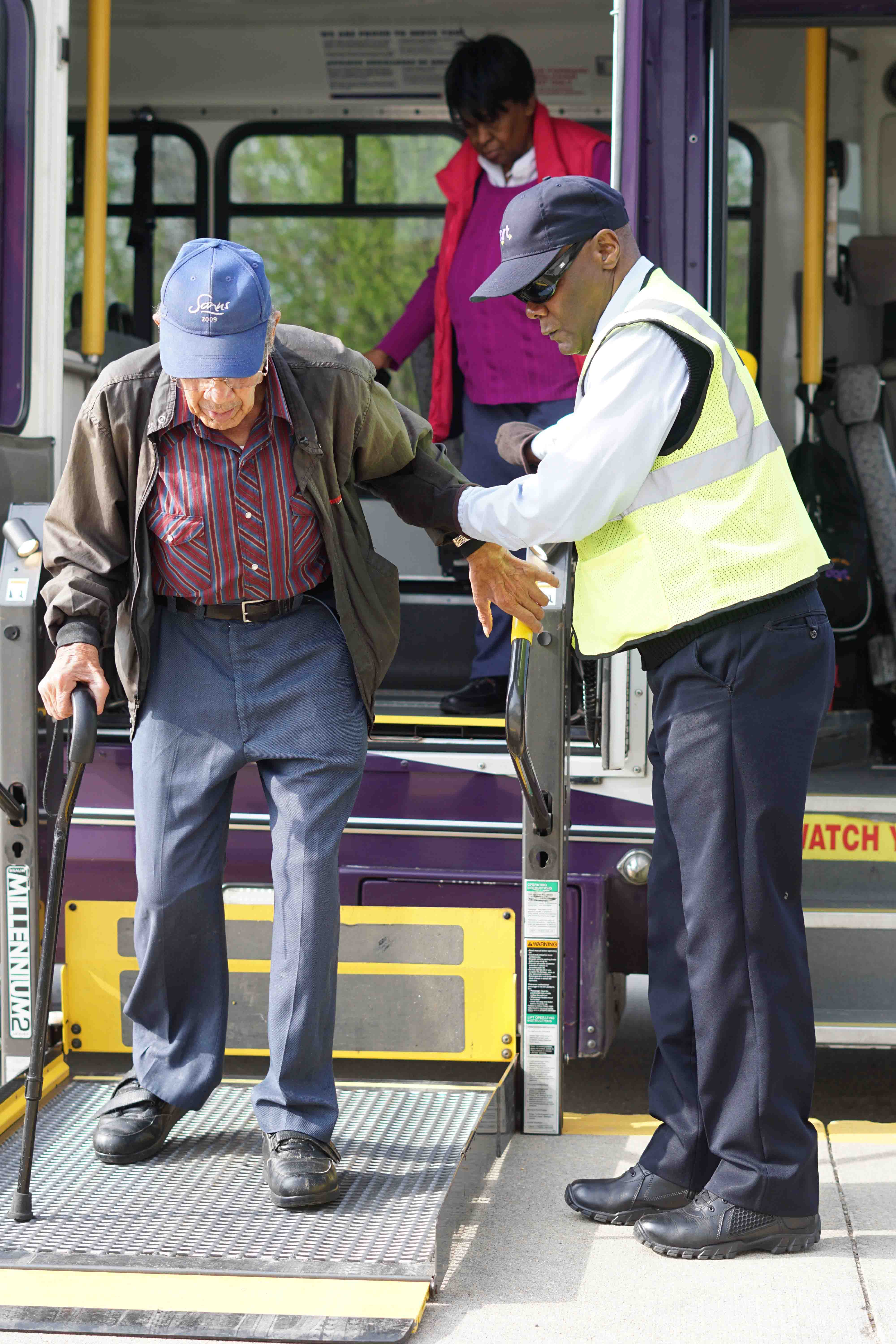 DART bus operator helps a man with a cane exit a Paratransit bus.